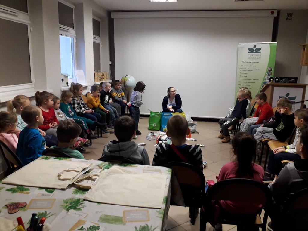 Dzieci na krzesłach biorą udział w zajęciach ekologicznych