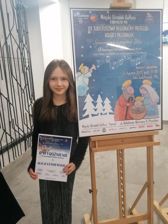 Alicja Leśniewska wraz z dyplomem za wyróżnienie stojąca obok plakatu konkursu