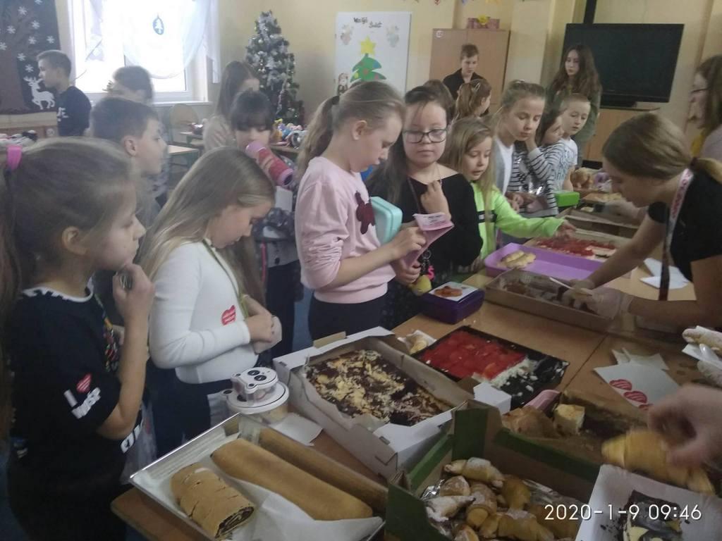Dzieci przy stołach ze słodkościami przeznaczonymi na licytację