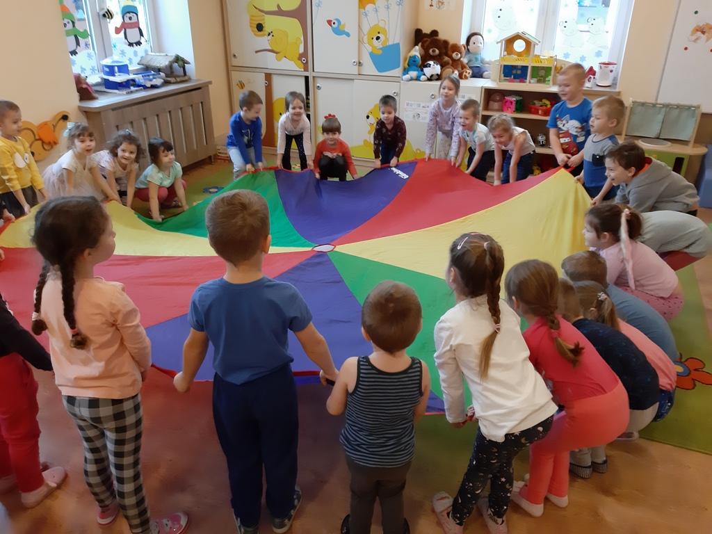 Przedszkolaki trzymające kolorowe koło z materiału