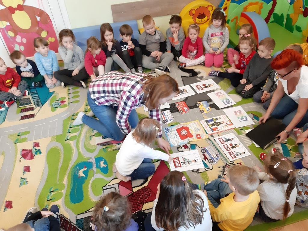 Postacie dzieci i opiekunek siedzących na dywanie z rozłożonymi numerami alarmowymi