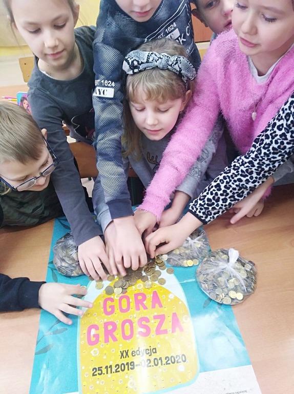 Dzieci z wyciągniętymi rękoma, dotykającymi pieniądze rozsypane na plakacie z napisem góra grosza.