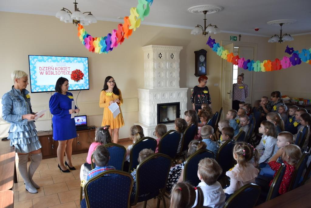 Zdjęcie przedstawia przedszkolaki wraz z paniami opiekunkami w sali pałacu na przedstawieniu z okazji dnia kobiet