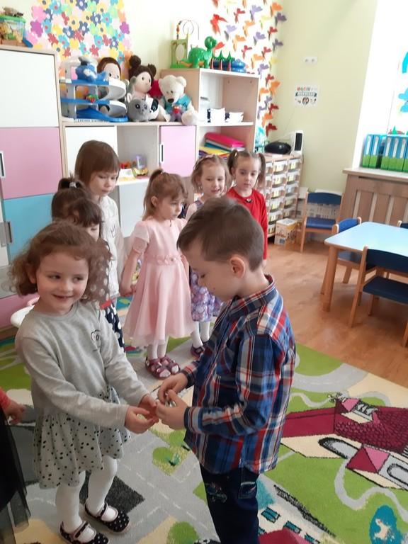 Zdjęcie przedstawia dzieci trzymające się za ręce a tuz przed nimi chłopiec wręcza dziewczynce bransoletkę