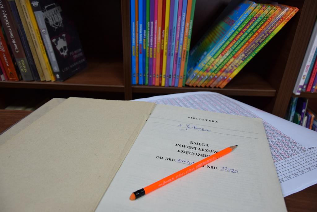 Zdjęcie przedstawia otwarty spis inwentarzowy książek a na niej ołówek natomiast w tle półka z książkami