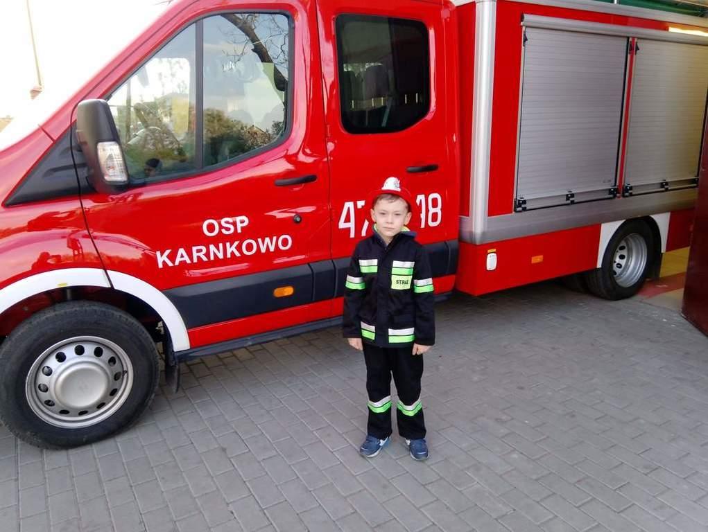 Zdjęcie przedstawia przedszkolaka ubranego w strój strażacki na tle samochodu strażackiego
