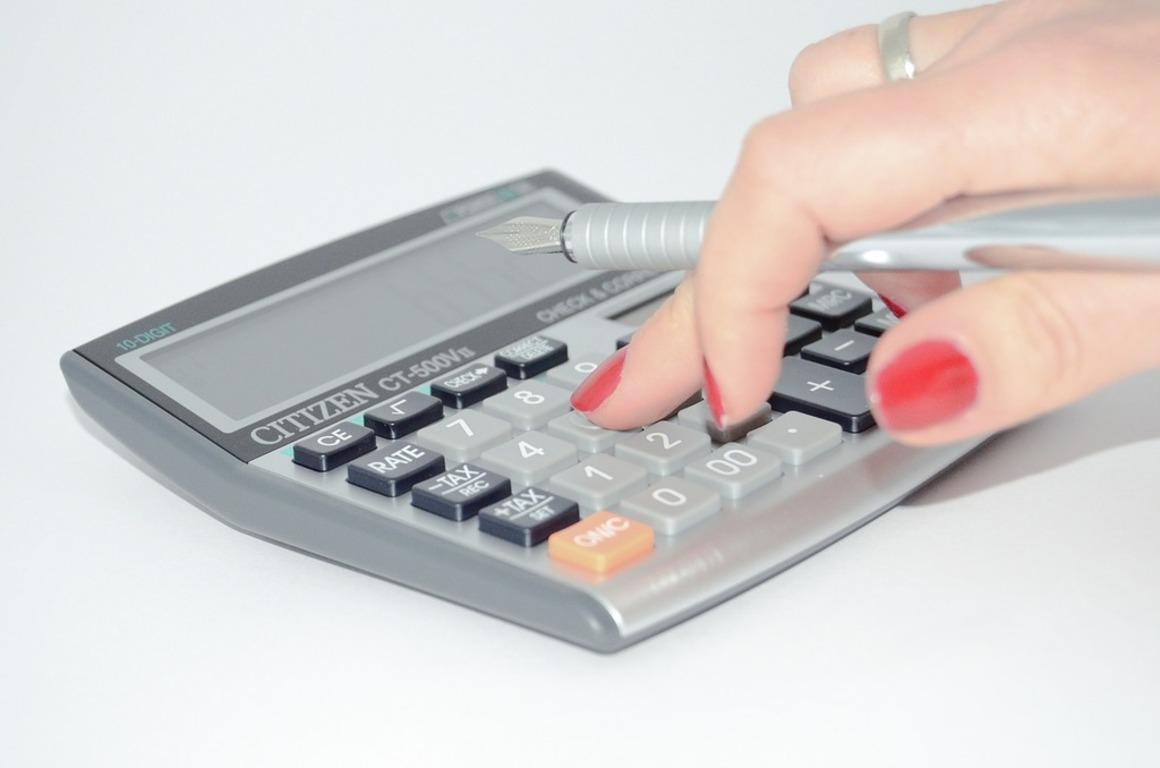 Widok dłoni wciskającej klawisze kalkulatora trzymające długopis