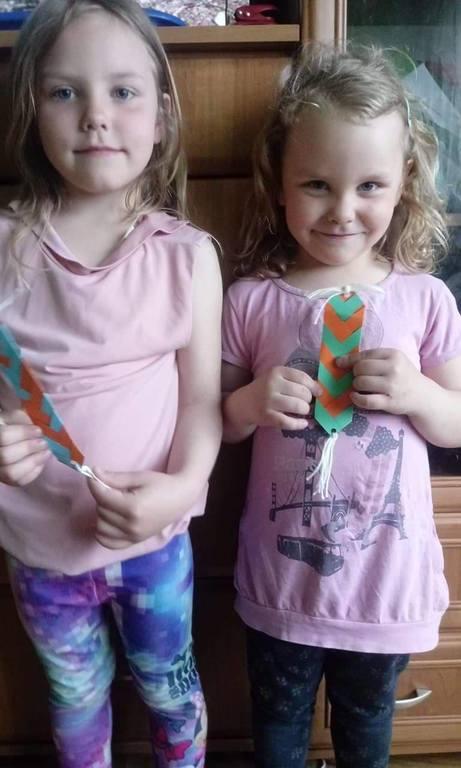 Dwie dziewczynki pokazujące własnoręcznie wykonane zakładki do książek.