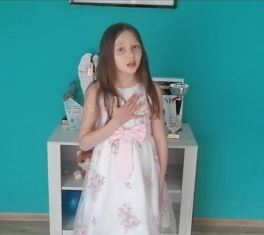 Dziewczynka  w białej sukience stoi i  śpiewa pieśń dla Jana Pawła II