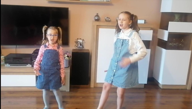 Dwie dziewczynki, które stoją i śpiewają piosenkę. Ubrane są w sukienki, mają takie same fryzury