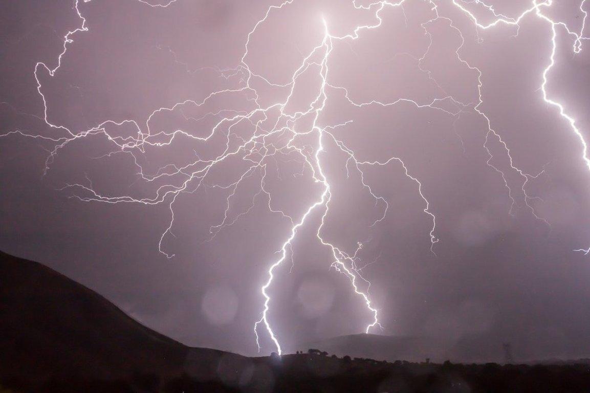 Pioruna na ciemnym niebie oznaczający burzę