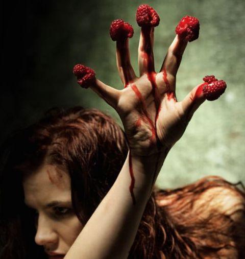 Zdjęcie dziewczyny z nałożonymi malinami na opuszki palców jednej dłoni