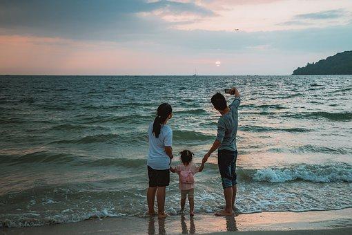 Postacie trójki osób, mężczyzny , kobiety i dziecka trzymających się za ręce. Mężczyzna robi zdjęcie całej trójce