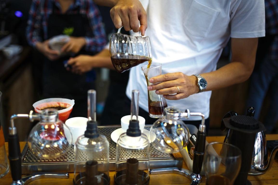 Postać mężczyzny nalewający świeżo zaparzoną kawę z dzbanka