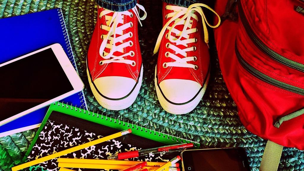 Czerwone buty, obok widoczne artykuły szkolne takie jak długopis i ołówek.