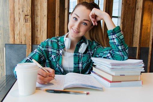 Młoda dziewczyna przy otwartym zeszycie, obok kilka książek ułożonych na sobie.