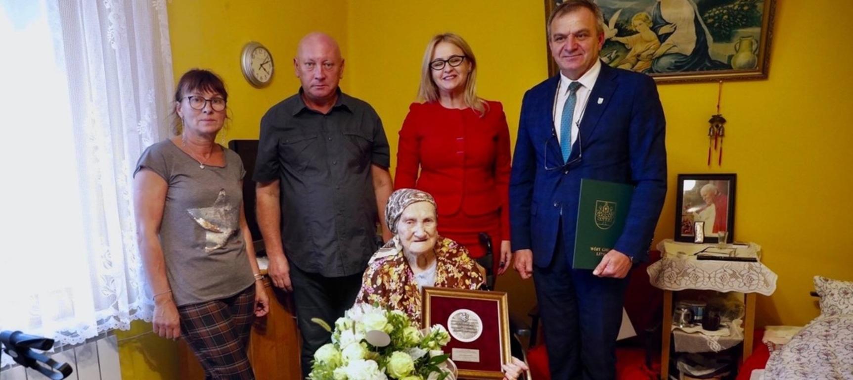 Pani Irena na wózku w towarzystwie Wójta Gminy Lipno oraz Pani Anety Jędrzejewskiej i domownikami.