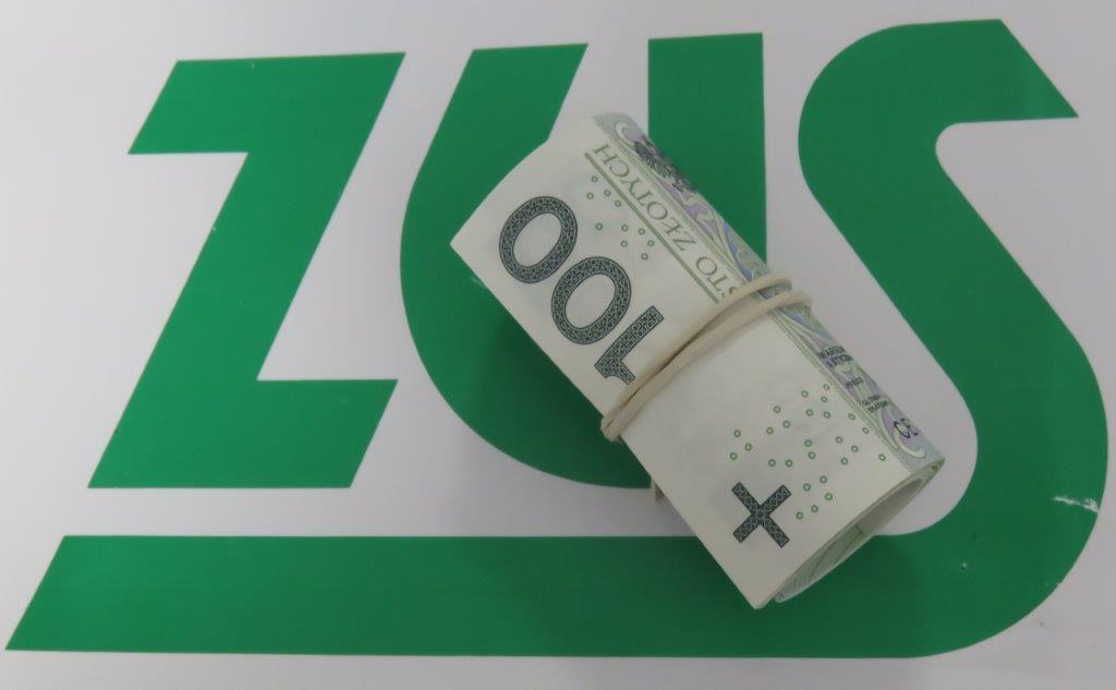 Rulon banknotów na tle logo ZUS.