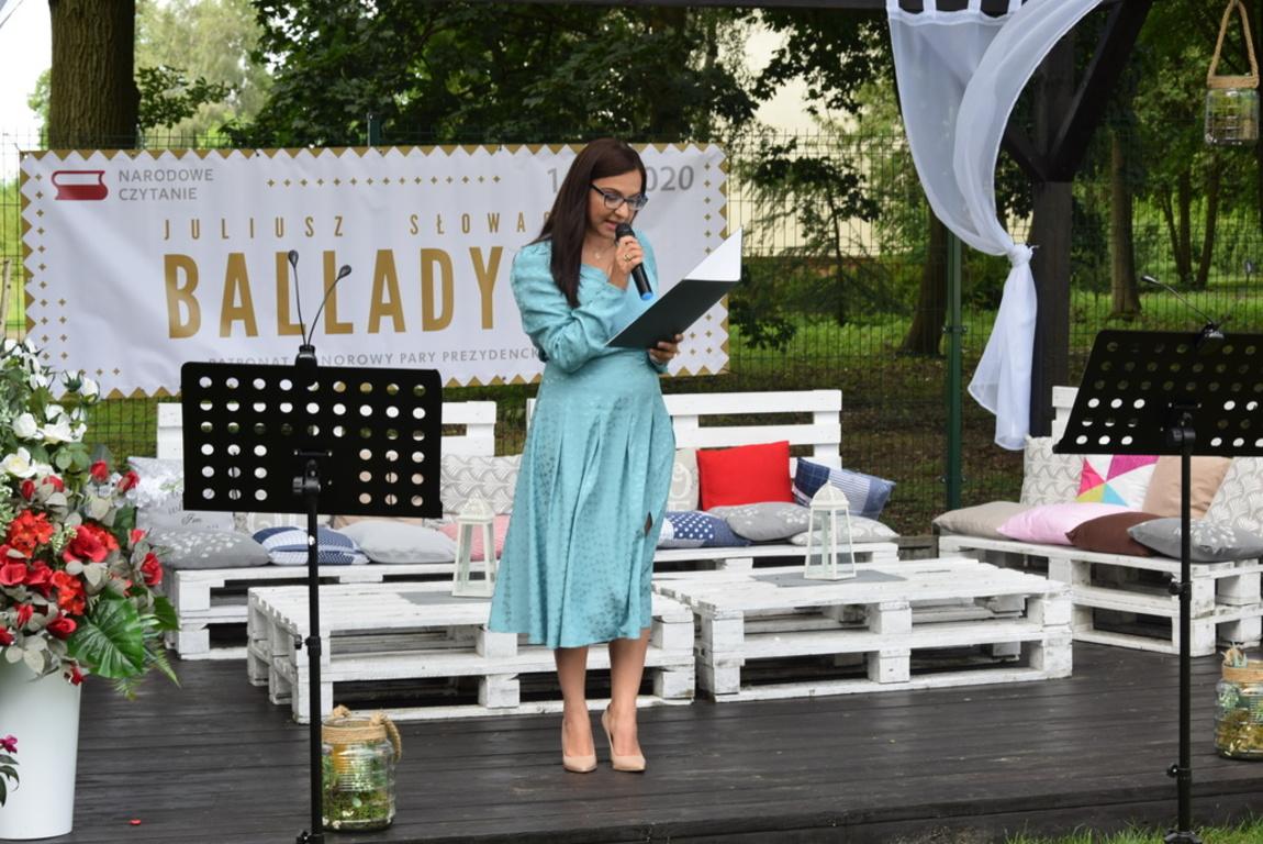 Na zdjęciu Dyrektor Biblioteki Publicznej Ewa Rozen – Bieńkowska stojąca w altanie, na tle parku. W tle dekoracja w postaci ławek , poduszek, lampionów, firanek.
