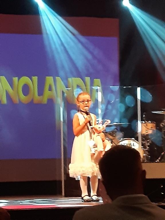 Mała dziewczynka w białej sukience stoi na scenie i śpiewa piosenkę