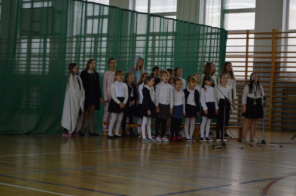 Grupa dzieci: chór szkolny stoi i śpiewa piosenkę. Wszyscy ubrani na biało – czarno.