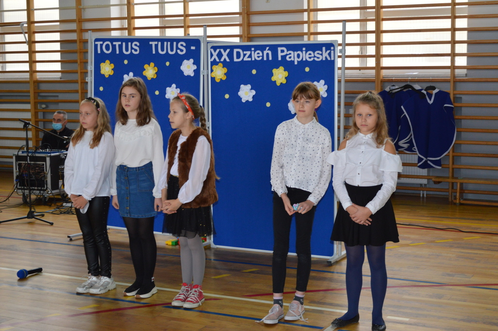 Na zdjęciu stoi pięć dziewczynek ubranych w białe bluzki i czarne spodnie lub spódnice.  Z tyłu na niebieskim tle napis: Totus Tuus – XX Dzień Papieski