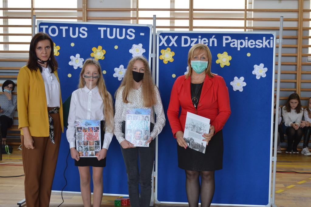 Na zdjęciu są cztery osoby: po bokach dwie dorosłe kobiety, w środku dwie uczennice, które trzymają w ręku dyplomy i książki