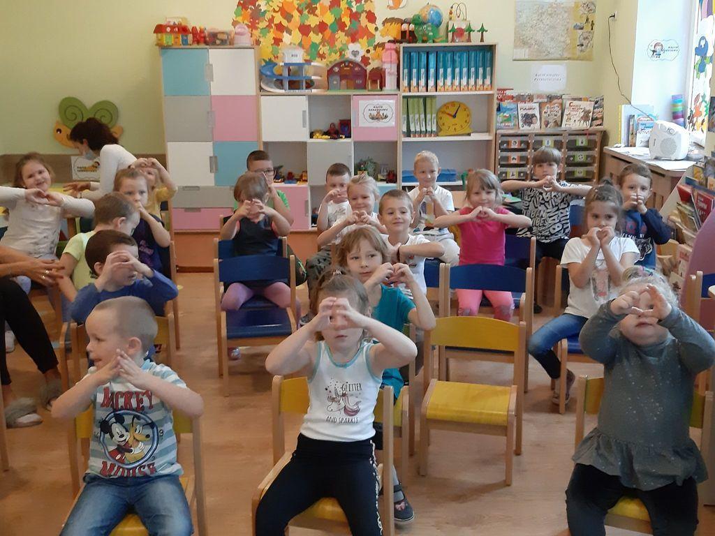 Na pierwszym palnie dzieci siedzące na krzesełkach. Zdjęcie zostało zrobione w klasie lekcyjnej przedszkolaków z Samorządowego Przedszkola w Karnkowie. Dzieci trzymają ręce na kształt serduszka.