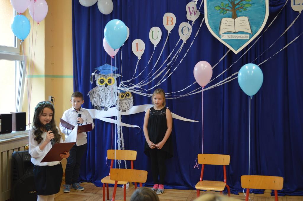 Troje dzieci na tle niebieskiej aranżacji podczas ślubowania