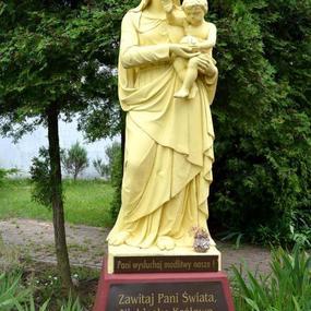Żółta figura Matki Boskiej przed kościołem w Kuklówce