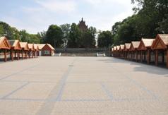 Targowisko w Łeknie. Plac targowy z drewnianymi wiatami. Z tyłu widoczny kościół parafialny pw. Św. (link otworzy duże zdjęcie)