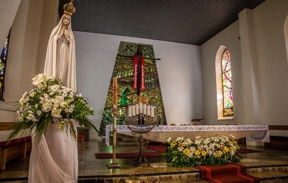 Kościół z wewnątrz z ołtarzem na drugim planie, a Matką Boską na pierwszym