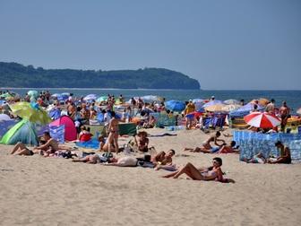 Turyści wypoczywający na plaży we Władysławowie, w tle przylądek Rozewie.