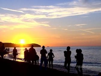 Widok na zachód słońca na plaży we Władysławowie, na horyzoncie przylądek Rozewie.