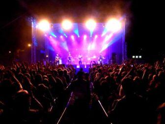 Koncert zespołu muzycznego ukazujący kolorowe światła i wizualizacje towarzyszące występującemu ze