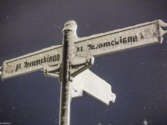 Słup z nazwami ulic pokryty śnieżnym puchem.