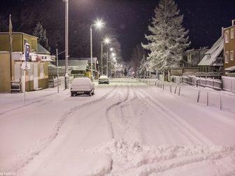 Ulica Sportowa wieczorową zimową porą, pokryta śnieżnym puchem.