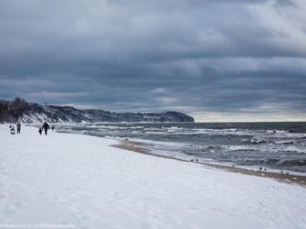 Plaża pokryta śniegiem w sąsiedztwie wzburzonego morza, na horyzoncie przylądek Rozewie.