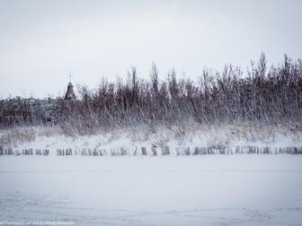 Wydmy na plaży pokryte śniegiem, w tle wierzchołek wieży Domu Rybaka.