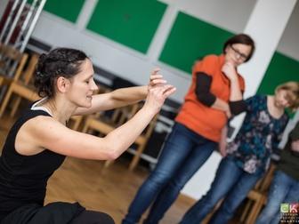 Prowadząca przedstawiająca jedno z ćwiczeń podczas warsztatów teatralnych.