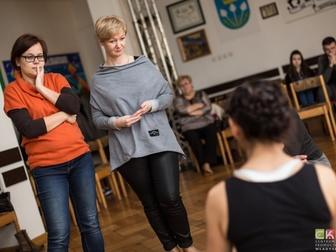 Uczestnicy spoglądający na prowadzącą w trakcie ćwiczeń podczas warsztatów teatralnych.