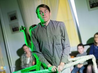 Mężczyzna z zaskoczoną miną stoi w pustym sześcianie i przedstawia jedną ze scen spektaklu.