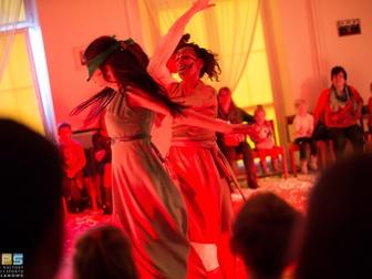 Dwie kobiety - jedna z pomalowaną twarzą, druga z opaską na oczach przedstawiają jedną ze scen spekt