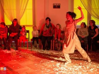 Kobieta z pomalowaną twarzą i uniesioną w bojowym nastawieniu odgrywa jedną ze scen przedstawienia.