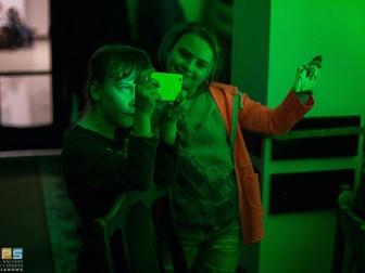 Dwójka dzieci z telefonami komórkowymi dokumentujący urządzeniami przedstawiany spektakl.
