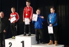Na zdjęciu młodzi zapaśnicy stojący na podium.