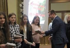 Na zdjęciu Wicestarosta Kraśnicki Karol Rychlewski wręczający uczennicom książki.