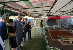 Na zdjęciu uczestnicy uroczystości oglądający makietę gospodarstwa.
