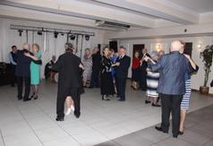 Tańczący seniorzy podczas zabawy karnawałowej.