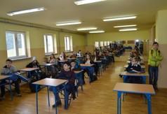 Uczniowie siedzący w ławkach.